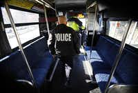 DART police Sgt. John Kusewitt, followed by Officer P.C Wong, disembarks from a bus at Mockingbird Station after waking a passenger who had snoozed through two complete trips.
