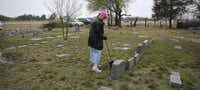 Sherry Johnston swept leaves and dirt away from a tombstone during Saturday's cleanup at the cemetery.