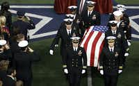 Taya Kyle, top left, wife of former Navy Seal Chris Kyle watch as the honor guard carries her husbandÕs coffin during the memorial service on Monday, February 11, 2013 at Cowboys Stadium in Arlington, Texas. (David Woo/The Dallas Morning News)David Woo - Staff Photographer