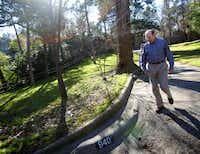 Dr. Robert Haley walks down the drive of the home he lived in while in high school in Oak Cliff.