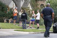 Residents along the street gather to discuss the day's events as officials guard the residence at 5700 block of  Marquita, where reportedly a person diagnosed with Ebola lived, photographed in Dallas on Sunday, October 12, 2014.  (Louis DeLuca/The Dallas Morning News)Louis DeLuca - Staff Photographer