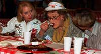 Prissy Shaffer (left) and Suzanne Hough (right) watch Julia Child take a bite of chocolate cake at the chocolate cake competition held Sunday afternoon at the Creative Arts building at the State Fair. The three tasted the top five cakes and chose a best of show winner. A couple of hundred people crammed the Creative Arts building to get a glimpse of Julia and to attend her book signing.