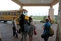 Students displaced by the tornado waited for a school bus Friday at the Best Western where their families are living temporarily.