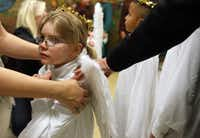 Six-year-old Emily Bone-Richardson is fitted with angel wings for the Christmas pageant at Cathedral of Hope.