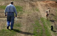 Robert Hutchins walks with two of his goats on his ranch, Rehoboth Ranch, near Greenville, Texas.