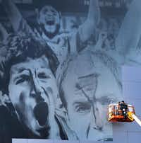 Workers spent part of Wednesday putting a March Madness mural on AT&T Stadium, where the Final Four of the NCAA men's basketball tournament will take place April 5 and 7. The tourney opens at a fast-break pace Thursday.Tom Fox - Staff Photographer