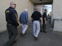 Kaufman county law enforcement officials escort an employee inside the Kaufman County Courthouse on Monday.