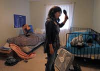 Elise Jones (right) gets ready for the day in her room at the Goodman House in Plano as roommate West Williams wakes up.