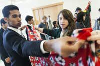 Saqib Vikaruddin, 17, and Liz Livingston,17, fold a blanket they are making for a children's hospital as part of a service project along with Muslim teens from the Deen Institute of North America and Jewish teens from the Academy of Torah in Dallas. They met at the Levine Academy to compare and learn about their faiths on Sunday.