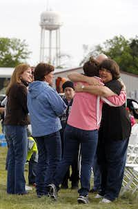 Sharon Middlebrook, center, gives a hug to the pastor's wife, Lisa Crowder, right,  prior to an outdoor service, on April 21, 2013, for the First Baptist Church of West, which was damaged by a fertilizer plant explosion. (Michael Ainsworth/The Dallas Morning News)Michael Ainsworth - Staff Photographer