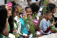 """Students from Paul Lawrence Dunbar Learning Center """"Diamonds and Studs"""" Mentoring Group waited for Laura Bush to speak Saturday and held onto live oak seedlings they were to plant later."""