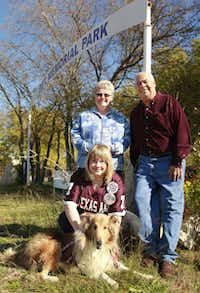 Theresa Brandon (standing), Gil Hernandez and Elizabeth Haley, with her dog Lucy, stand outside Pet Memorial Park in Cedar Hill. State ordinances protecting burial grounds apply only to those with human remains. An auction has been delayed to give supporters time to raise money to purchase the cemetery.