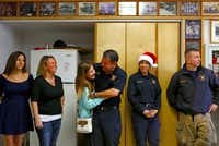 Dallas Fire-Rescue Lt. Ladd Smith hugged his daughter, Claire, as they waited for Christmas dinner Wednesday at Station 11. Also pictured are (from left) Kristen Smith, Jennie Smith, Mari Sanchez and John Hampton.