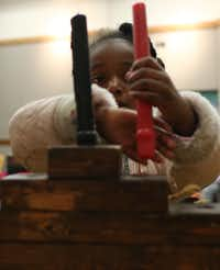 Lillian Pryor, 5, puts the second candle in during Wednesday's Kwanzaa celebration at the Highland Hills library.
