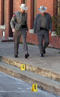 Law enforcement officers walked past some evidence markers that were placed in downtown Kaufman after Kaufman County assistant district attorney Mark Hasse was gunned down outside the county courthouse on Jan. 31.