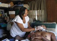 """Terina Taylor cleans around her son Willie's ventilator tube at her home. Terina has benefited from a nonprofit group that helps moms caring for ill children. """"Just the release of being with others who I understand and who understand me,"""" she said. """"It was life-altering almost. I wasn't alone.""""Evans Caglage - Staff Photographer"""