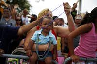 Dominic Garza, 14 months, wears beaded necklaces that his grandmothers Kristin Weatherly and Helen Garza collected during the 30th annual Dallas gay pride parade.
