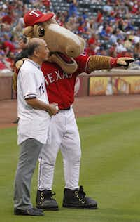 """Japanese Ambassador Kenichiro Sasae get a pointer from Texas Rangers mascot """"Champ"""" as he prepared to throw out a ceremonial pitch during their MLB baseball game at Rangers Ballpark in Arlington on Wednesday."""