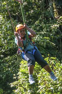 A visitor plays Tarzan, zipping from tree to tree through the rainforest on a Jungle Surfing Canopy Tour at Cape Tribulation.
