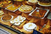 "Santiago de Compostela's signature dessert, the ""tarta de Santiago,"" is a delicious almond cake showcased in pastry shop windows throughout the city."