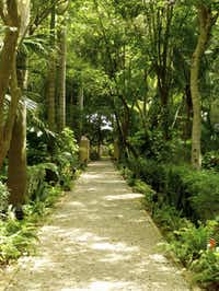 Pathways lead to surprises in the lush gardens at Hacienda Xcanatún.
