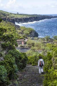 On Pico Island, guide Ana Carmo walks down a coastal path toward a building once used by early winemakers.Phil Marty