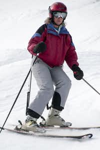 A CADS skier descends a slope. Originally designed to mitigate thigh burn, the package consists of a waist harness, cord, boot anchor, elasticized band and connecting rod.
