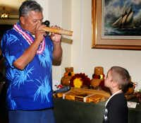 A native Hawaiian's nose flute performance fascinates a visiting boy.Irv Green  -  Special Contributor