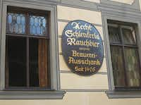 """In the old town section of Bamberg, a UNESCO World Heritage Site, you'll find this sign next to the Schlenkerla tavern, famous for its Rauchbier or """"smoked beer."""" The brewery was first mentioned in 1405."""