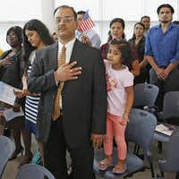 Four-year-old Aditi Ashok  waved the flag for her father, Ashok Vijaykumar of Plano, during a naturalization ceremony for new citizens at the Dallas district office of the U.S. Citizenship and Immigration Services in Irving.Andy Jacobsohn  -  Staff Photographer