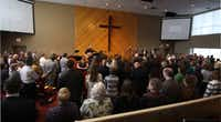 Worshippers stand and sing during Sunday service at NorthPointe Baptist Church in Arlington.