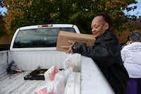 Mona Hill helps load food for her sister-in-law at Oak Cliff Churches for Emergency Aid.ROSE BACA