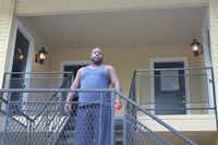 Oak Villas Apartments resident Lamarcus Jackson stands on the stairwell to his second-story apartment. Broken light fixtures have been replaced, but stay on all day and night, he said.