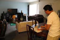 Francisco Gonzalez makes dinner for his daughter Leah Gonzalez in the dining room of thier two-bedroom unit at Oak Villas.