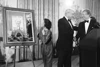 President Jimmy Carter shakes hands with the manager of his unsuccessful re-election campaign at a White House reception in Washington on Dec. 9, 1980. Mrs. Robert Strauss examines the Norman Rockwell painting the president presented to Strauss,Dennis Cook  -  ASSOCIATED PRESS