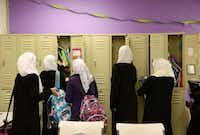 Students — dressed in black abaya robes with white scarves over their heads — visit their lockers between class periods. According to a 2010 religious census by the Association of Religious Data Archives, the Muslim population estimate in Dallas County totaled 25 congregations and more than 84,000 adherents.Rose Baca - neighborsgo staff photographer