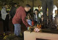 Trophy Club police Officer Keith Burris and his family place flowers Tuesday night at the The Spirit of Care statue outside the Euless Police Department. (Ron Baselice/The Dallas Morning News)