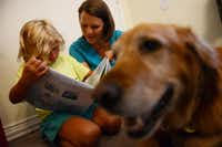 Angel Jones reads to Joni Brock and her dog, Sandy, a golden retriever.Rose Baca  -  neighborsgo staff photographer