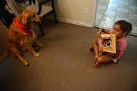 Arianna Crump, 6, reads When the Rooster Crowed to therapy dog Faith at The Samaritan Inn. Since last September, the therapy dogs have been part of a program at the shelter to improve children's reading skills.Rose Baca - neighborsgo staff photographer