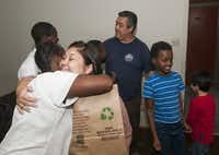 Patricia Bowlin  (facing camera), 17, hugs Yvonne Nyirangenerwa as Patricia and her father, Dary Bowlin, (background) deliver a Thanksgiving meal to the Nyirangenerwa familiy.