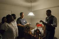 Translator Albert Musafi (right) helps Dary Bowlin (center) get his point across as he describes how to prepare Thanksgiving dinner to Yvonne Nyirangenerwa (left) and her husband, Joseph Runezerwa. What started a decade ago as Bowlin's small act of kindness for a co-worker going through a rough time has grown into a movement that today will help 100 families.
