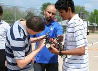 Instructor Jose Guerrero, center, helps team members Bullis and Carlos Lopez repair one of the team's cars during practice.Photo by RUTH HAESEMEYER - Special Contributor