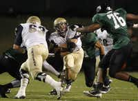 Jesuit running back Adam Holtz, center, carries the ball as offensive lineman Jack Summers (63) blocks and Berkner defensive lineman Rodney Derare moves in for the tackle in the first half of the football game between Richardson Berkner High School and Jesuit High School in Richardson Oct. 4.
