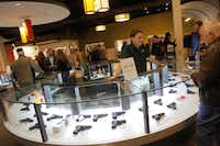 Clay Hunn worked at the handgun desk at the Frisco Gun Club on Friday at the club's grand opening.