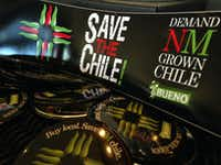In this July 31, 2013 image, a collection of bumper stickers and buttons promoting New Mexico-grown chile sits on the order counter at Hello Deli restaurant in Albuquerque, N.M. A friendly Super Bowl bet between the mayors of Seattle and Denver has created a stir this week in New Mexico, re-energized efforts to promote the state's famous hot peppers. (AP Photo/Susan Montoya Bryan)Susan Montoya Bryan - AP