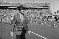 Dallas Cowboys coach Tom Landry walks across the turf at the Orange Bowl, Jan. 17, 1971, as he watches his team loosen up with calisthenics before engaging the Baltimore Colts in the Super Bowl V game.