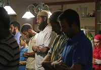 Daniel Abebe (center) joins other Muslims in prayer before a nightly iftar dinner at Sturm's home in Arlington.Brad Loper  -  Staff Photographer