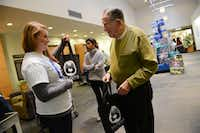 Carmen Finocchio of the Aaron Family Jewish Community Center of Dallas hands a Shabbat in a Bag to Harlan Holiner on Dec. 13. Each bag contained Challah bread a special braided loaf that is part of the Shabbat meal grape juice to represent wine, candles and a Kiddush, a blessing recited over the meal.ROSE BACA
