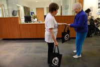 Bev Broman of the Aaron Family Jewish Community Center of Dallas hands a Shabbat in a Bag to Marcy Mandelstam on Dec. 13. Each bag contained Challah bread a special braided loaf that is part of the Shabbat meal grape juice to represent wine, candles and a Kiddush, a blessing recited over the meal.ROSE BACA