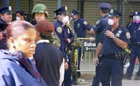 Pedestrians pass by police officers and armed military guarding New York's financial district (Fulton and Nassau) on Sept 17 after the World Trade Center attacks of Sept. 11. Many wear masks because of air quality concerns.